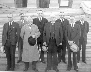 Eight middle aged white men, seven wearing three piece suits and one wearing an overcoat that obscures what he's wearing beneath, stand in two rows in front of some steps.