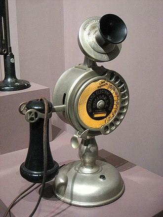 Telephone hook - An early telephone manufactured in 1909. The black earpiece is seen resting on the hook.