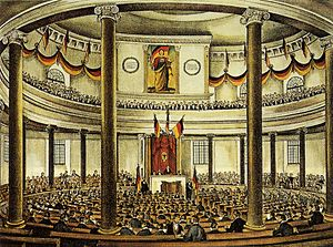 Germania (St. Paul's Church, Frankfurt am Main) - Frankfurt Parliament meeting in the Paulskirche decorated with the painting in 1848/49 (coloured, contemporary engraving). The yellow color on the flag is of contemporary imagination.