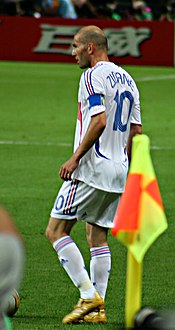 "A bald-headed man wearing a white shirt and white shorts with the number ""10"" displayed on the back of the shirt."