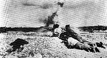 Photographie en noir et blanc d'hommes tirant des armes