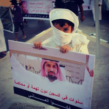 A sign board that has The Picture of Abdulla Majed Al Noaimi rising another board in one of his Human Rights protests. the sign board is held By a young brave eight years old kid.