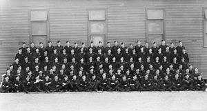 Formal portrait of six rows of men military uniforms, seated or standing in front of a building