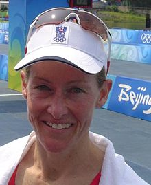 A blue-eyed smiling woman wearing a white towel around her shoulders and a white cap with a pair of white-framed sporting sunglasses on top of it. The cap bears the Austrian Olympic committee logo.