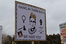 "A poster with ""hang in there we need you"" written around Ginsburg's face and a crown on her head"