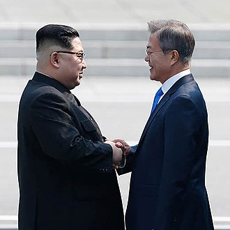 Sunshine Policy - Kim and Moon shake hands in greeting at the demarcation line.