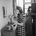 A female war worker fixes her hair in the bedroom she shares with another worker at the hostel attached to the Royal Ordnance Factory, Bridgend, in January 1942. D6332.jpg