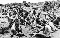 A group of Japanese prisoners who preferred capture to suicide wait to be questioned.