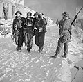 A wounded British officer being helped through the snow to a dressing station during the Vaagso Raid, Norway, 27 December 1941. N495.jpg