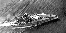 A low quality photograph of the battleship in the open seas, taken from above
