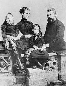 Een voorname bebaarde man, zijn jonge elegante vrouw naast hem, en hun twee jonge dochters poise voor een formeel portret
