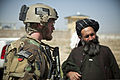An Afghan district governor, right, speaks with a coalition forces service member during a presence patrol with Afghan National Security Forces (ANSF) in Helmand province, Afghanistan, March 17, 2013 130317-M-BO337-125.jpg