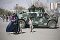 An Afghan women with children passing by ANA Humvee.jpg