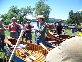 Old Town Canoe - Benson Gray, a descendant of the founders of Old Town Canoe, leads a tour of canoes on the green at the Annual Assembly of the Wooden Canoe Heritage Association, which featured Old Town's contributions to canoeing in 2012.