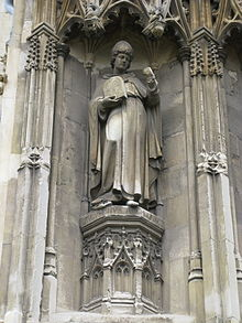 Stone statue of a standing man wearing robes and a mitre, carrying a tablet in one hand and holding his other hand up.
