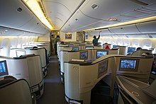 Airliner cabin. Rows of seats arranged between two aisles.