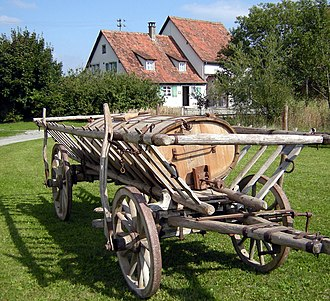 A hay wagon in Germany, of a type common throughout Europe (the leiterwagen). The sides are actually ladders attached to serve as containment of hay or grain, and may be removed, such as for hauling timber. Bad Schussenried - Museumsdorf Kurnbach Holz Jauchefass auf Leiterwagen.jpg