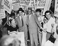 Two men dressed in suits are surrounded by persons holding signs.