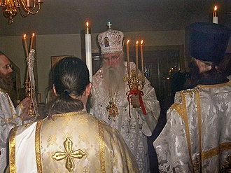 Paschal trikirion - Eastern Orthodox bishop holding a paschal trikirion with two deacons (backs to camera) holding paschal deacon's candles.