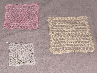 Blocking (textile arts) - Crochet samples during blocking.  After soaking in hot water these items were shaped and laid to dry on a towel.  Pins hold some examples in the desired shape.