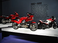 "Three sporty motorcycles of the 1990s on pedestals.  Text on the wall behind them says ""1982-1989"" with a few dozen words relevant to the period, such as ""Atari"", ""MTV"", and ""Robert Mapplethorpe""."