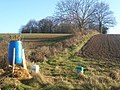 Blue barrel and slope up to copse - geograph.org.uk - 1071261.jpg