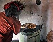 Elektrikli ocakta ekmek pişiren kadın