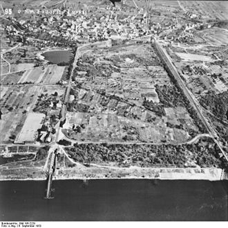 "Neuenburg am Rhein - Aerial view of the city from the west from a Rhine overflight of the Allies (September 6, 1953): on the left the road to Chalampé with parts of the provisional pontoon bridge over the Rhine, at the top left the ""Wuhrloch"", at the bottom left a corner of the now no longer existing Rhine port, on the right the railway line of Mulhouse with shadows of the remnants of the railway bridge over the Rhine, which was blown up by the Wehrmacht on their retreat on February 9, 1945 (picture dated before the completion of the Grand Canal d'Alsace)"
