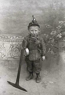 A child holding a pickaxe with a pipe in his mouth