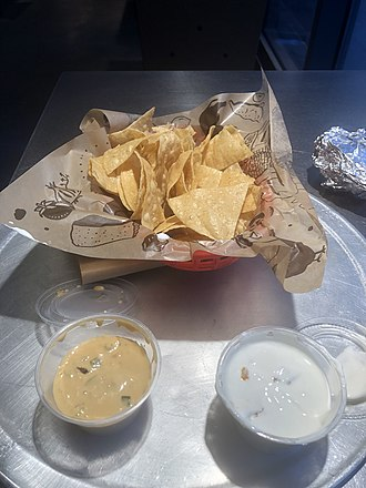 Chipotle Mexican Grill - Chipotle regular sized chips and queso with a side of sour cream.
