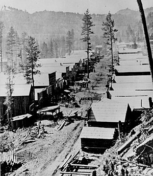 Deadwood, South Dakota - A photograph of Deadwood in 1876. General view of the Dakota Territory gold rush town from a hillside above.
