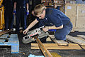 Defense.gov News Photo 100506-N-6604E-053 - U.S. Navy Petty Officer 3rd Class Ashley Owens uses a portable band saw to cut metal in the hangar bay of the aircraft carrier USS Dwight D.jpg