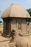 Small stone domed building, with a carved bull in the foreground