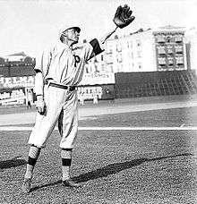 "A man wearing a baseball uniform bearing the letter ""P"" on the chest leans slightly to his left and raises his left hand on which he is wearing a baseball glove."