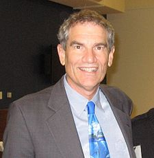 A photo of Duane Silverstein wearing a grey suit and a blue tie.
