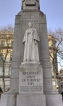 A marble statue of Edith Cavell in nurse's uniform backed by a large granite column