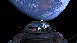 Photograph of the black emptiness of space, with planet Earth partly in shadow in the background. In the foreground is an open-top red convertible sports car, viewed from the front over the hood, with a mannequin in the driving seat that is wearing a white-and-black spacesuit