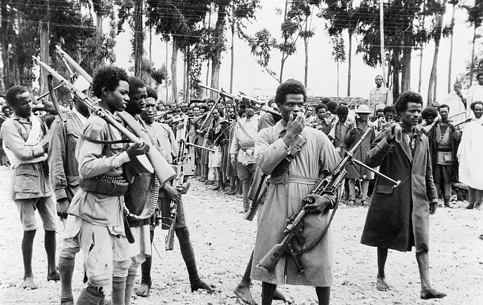 Ethiopian men gather in Addis Ababa, heavily armed with captured Italian weapons, to hear the proclamation announcing the return to the capital of the Emperor Haile Selassie in May 1941. K325