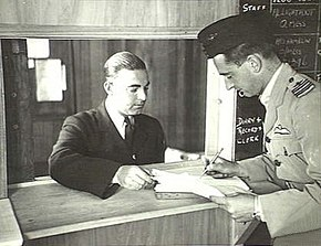 Two men in military uniforms, one wearing a forage cap and filling out a form
