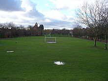 A long narrow strip of grass stretches into the distance, with houses on both sides. The grass is occupied by football pitches