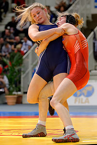 Photograph of two female wrestlers grappling each other