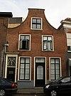 foto van Huis met gaaf bewaarde tuitgevel met deur, voorzien van klopper en neo-gotisch bovenlicht