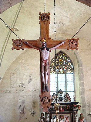 "Rood - The 800-year-old cross in the Church of Stenkumla on Gotland shows the origin of the name Christus triumphans: the crucified figure wears a crown and ""shoes""."