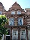 foto van Huis 'in den gulden engel', onder zadeldak en met trapgevel van het 'Dordtse' type, met natuurstenen banden, waterlijsten en blokken, geprofileerde korfboogvormige ontlastingsbogen