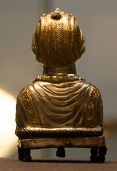 The golden back of a statue of a lady made from metal standing on dumpy feet