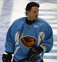 A Caucasian hockey player shown from the waist up. He is helmet-less and wears a blue jersey with a stylized brown thrasher holding a hockey stick as a logo