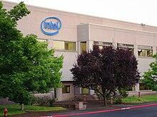 Oficina de estuco beige en el campus de Hawthorn Farm de Intel Corporation.  El edificio incluye el logo de la empresa en el exterior.