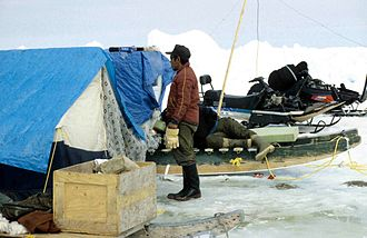 Qamutiik - A hunter's camp at a floe edge, qamutiik with tarp-covered boxes. Snowmobiles in background.
