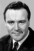 Black and white portrait of Jack Lemmon--a white man with a broad forehead and round face, short dark hair parted on his left, with dark eyes, smiling slightly, and wearing a dark suit, around 43 years of age--in 1968.