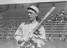 "A black-and-white photograph of a man wearing a baseball sweater with a ""P"" over the left breast and a crownless baseball cap holding a baseball bat over his left shoulder"